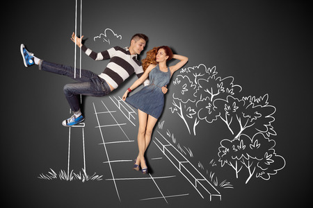 Happy valentines love story concept of a romantic couple against chalk drawings background. Male pole dancing on a lamppost while walking with girlfriend.