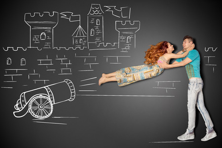 Happy valentines love story concept of a romantic couple against chalk drawings background. Male catching his girlfriend launched as a human cannonball. Archivio Fotografico