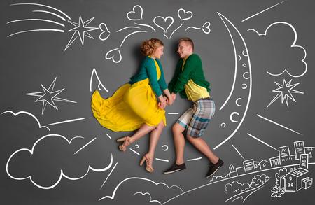 day night: Happy valentines encanta concepto historia de una pareja rom�ntica, sentado en la luna y de la mano contra dibujos de tiza de fondo de un cielo nocturno. Foto de archivo