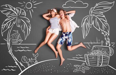 amantes: Happy valentines encanta concepto historia de una pareja rom�ntica en una isla desierta, compartiendo auriculares, y escuchando la m�sica contra dibujos de tiza de fondo de un mar y un cofre del tesoro.