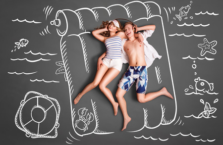 Happy valentines love story concept of a romantic couple lying on an air mattress, sharing headphones, and listening to the music against chalk drawings pool background.