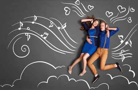 Gelukkige Valentijnsdag liefdesverhaal concept van een romantische paar delen koptelefoon en luisteren naar de muziek tegen krijttekeningen achtergrond van notities, speler iconen en wolken. Stockfoto