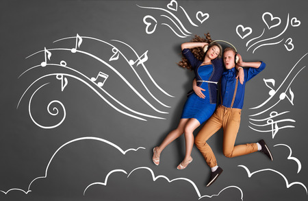 Happy valentines love story concept of a romantic couple sharing headphones and listening to the music against chalk drawings background of notes, player icons and clouds. Stock Photo - 41118111