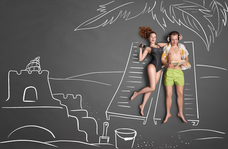 sun beach: Love story concept of a romantic couple against chalk drawings background. Male lying on sun lounger, wearing headphones and reading a book, female taking picture of a sand castle. Stock Photo