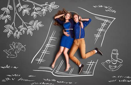 amantes: Valent�n amor feliz concepto de historia de una pareja rom�ntica en un picnic compartiendo auriculares y escuchando la m�sica contra el fondo de dibujos de tiza.