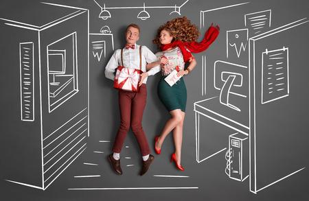 Gelukkig Valentijnsdag liefdesverhaal concept van een kantoor romantiek. Jong stel op het werk lachend naar elkaar en het delen van geschenken tegen krijttekeningen kantoor achtergrond.