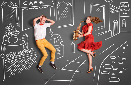 lovers: Love story concept of a romantic couple against chalk drawings background. Woman playing the sax on the street for her lover. Stock Photo