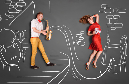 love story: Love story concept of a romantic couple against chalk drawings background. Male playing the sax in a restaurant for his girlfriend.