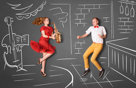aucasian: Love story concept of a romantic couple against chalk drawings background. Female playing the sax in a restaurant for her boyfriend.