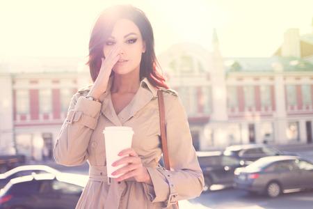 美しい若い女性現代のトレンチ コート、使い捨てのテイクアウト カップを保持していると都市背景に立っています。