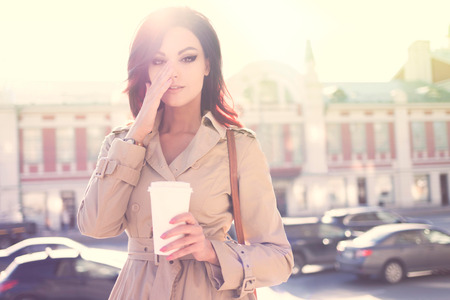 trench coat: Beautiful young woman in a modern trench coat, holding a disposable takeaway cup and standing against urban city background. Stock Photo