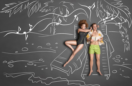 loungers: Love story concept of a romantic couple lying on sun loungers against chalk drawings background. Male listening to the music in the headphones and reading a book, female trying to gain his attention.