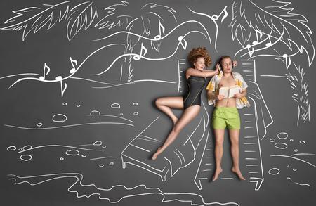 Love story koncept romantický pár ležící na lehátkách proti křídové kresby pozadí. Muž poslechu hudby ve sluchátkách a čte knihu, žena snaží získat jeho pozornost. Reklamní fotografie