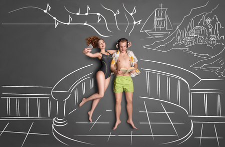 bikini top: Love story concept of a romantic couple on shore against chalk drawings background, top view. Male wearing headphones and reading a book, female taking selfie with a smartphone. Stock Photo