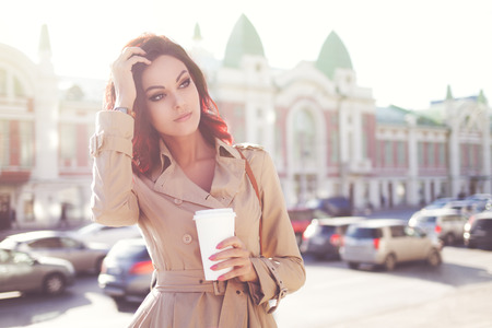 Beautiful young woman in a modern trench coat, holding a disposable takeaway cup and standing against urban city background. Stok Fotoğraf