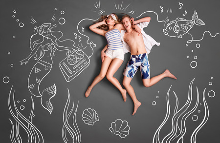 two story: Happy valentines love story concept of a romantic couple swimming underwater, sharing headphones, and listening to the music against chalk drawings undersea background.