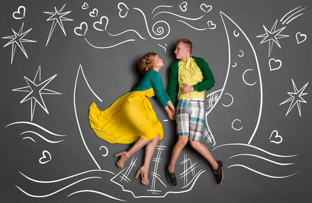 romantic date: Happy valentines love story concept of a romantic couple swimming on the moon boat, holding hands and kissing against chalk drawings background of a night sky.