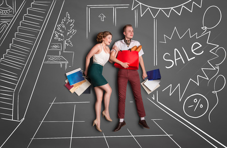 Love story concept of a romantic couple on shopping against chalk drawings background. Young happy couple standing together with shopping bags in a shopping mall during sales. Фото со стока
