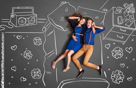 happy couple: Happy valentines love story concept of a romantic couple lying in bed, sharing headphones, and listening to the music against chalk drawings room background. Stock Photo