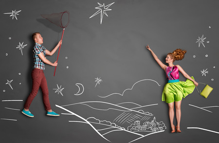 Happy valentines love story concept of a romantic couple catching stars with a butterfly net against chalk drawings background of a night sky. Foto de archivo