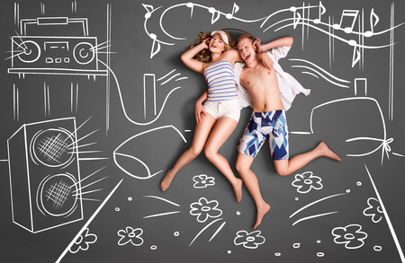 bedroom bed: Love story concept of a romantic couple lying in bed, sharing headphones, and listening to the music against chalk drawings background of a bedroom with acoustic system. Stock Photo