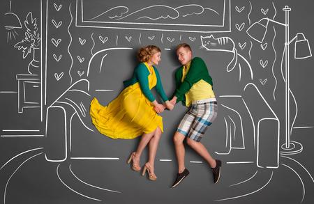 Happy valentines encanta concepto historia de una pareja romántica, sentado en un sofá y la celebración de las manos contra dibujos de tiza de fondo de una sala de estar. Foto de archivo