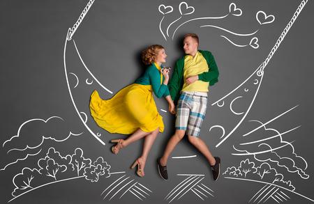 baiser amoureux: Happy valentines amour concept de l'histoire d'un couple romantique se balancer sur la lune, tenant les mains et embrassant contre dessins à la craie fond d'un ciel de nuit.