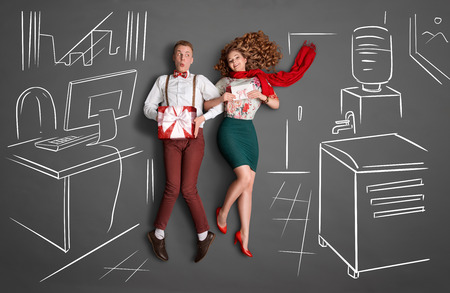 romance: Happy valentines encanta concepto historia de un romance de oficina. Pareja joven en el trabajo sonriendo el uno al otro y compartir presenta contra dibujos de tiza de fondo.