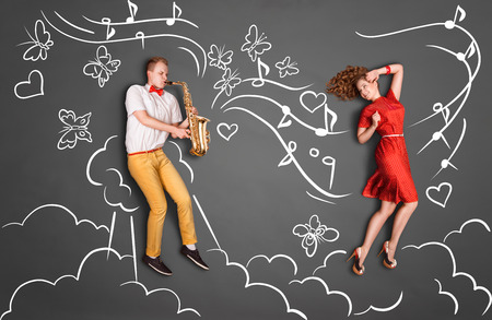 girlfriend: Love story concept of a romantic couple against chalk drawings heaven background. Male playing the sax for his girlfriend.