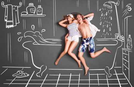 shower: Happy valentines love story concept of a romantic couple in a bathroom, sharing headphones, and listening to the music against chalk drawings room background.