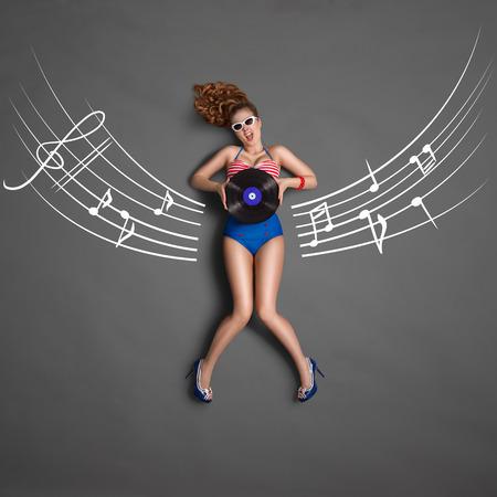 pentagrama musical: Pin-up girl hermosa en bikini retro y gafas de sol, sosteniendo un disco de vinilo LP microsurco y sentado en musical tiza personal dibujos de fondo, vista desde arriba. Foto de archivo