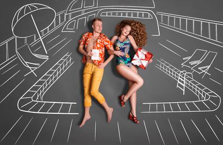 parejas romanticas: Concepto de amor historia de una pareja rom�ntica contra dibujos de tiza de fondo. Pareja joven en compartir vacaciones de regalos sobre un fondo de la piscina.