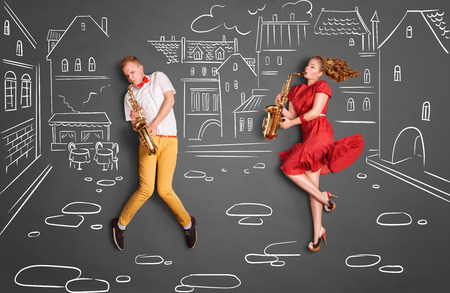 Love story concept of a romantic couple against chalk drawings background. Musician couple playing serenade on saxophone on city streets.