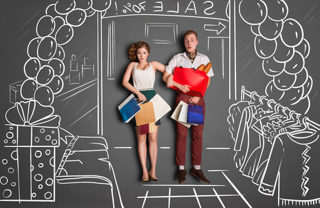 Love story concept of a romantic couple on shopping against chalk drawings background. Young couple with shopping bags entering a shopping mall during sales. photo