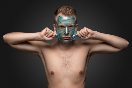 male facial: Portrait of a beautiful young man peeling off a facial mask, face and body skin care retreat.
