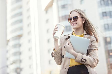 美しい若い実業家使い捨てのコーヒー カップでコーヒーを飲みながら、都市の背景に彼女の手でタブレットを保持しています。 写真素材