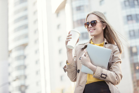 Beautiful young businesswoman with a disposable coffee cup, drinking coffee, and holding tablet in her hands against urban city background.