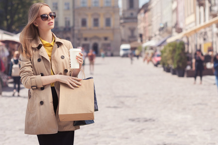 �aucasian: Young fashionable woman taking a coffee break after shopping, walking with a coffee-to-go in her hands against urban city background. Stock Photo