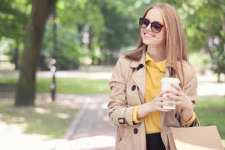 take a: Young fashionable woman taking a coffee break after shopping, walking with a coffee-to-go in her hands against green city park background.