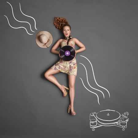 highend: Beautiful girl, wearing vintage music headphones around her neck and holding a purple LP microgroove vinyl record on chalkboard background with playing high-end gramophone drawing, top view. Stock Photo