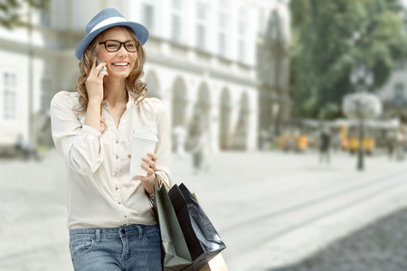 Happy young woman with a disposable coffee cup and shopping bags, talking on phone and smiling against urban city background.
