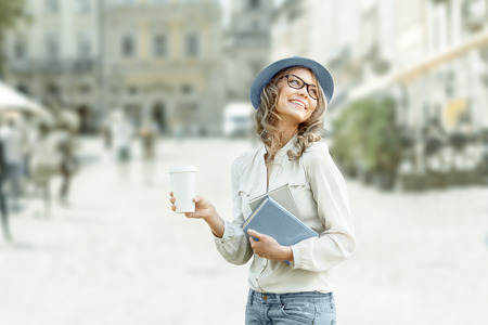 urban fashion: Happy young student with a coffee-to-go, holding books for reading and studying against urban city background.