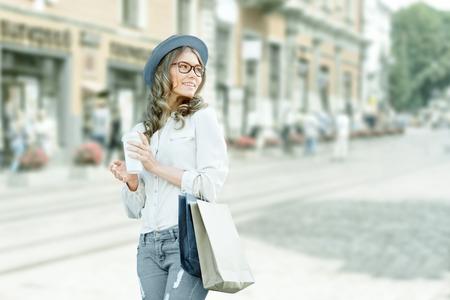 comprando: Mujer de moda joven feliz tomando un caf� despu�s de las compras, sonriendo con un caf�-to-go en sus manos contra el fondo urbano de la ciudad.