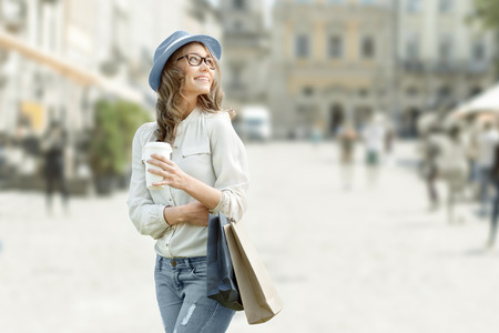 fashion style: Happy young fashionable woman with shopping bags enjoying drinking coffee after shopping and holding take away coffee against urban background. Stock Photo