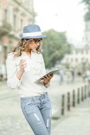 personas leyendo: Joven y bella mujer con una taza de caf� desechables, que sostiene la tablilla en sus manos, la lectura de noticias y estudiando contra el fondo urbano de la ciudad. Foto de archivo