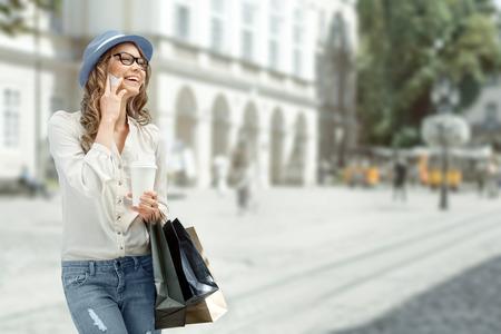 chicas comprando: Mujer joven feliz con una taza de café y de compras bolsas desechables, hablando por teléfono y sonriente contra el fondo urbano de la ciudad.
