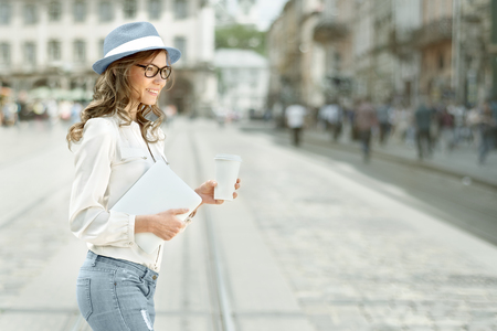 girl in a hat: Beautiful young woman with a disposable coffee cup, drinking coffee, holding tablet in her hands, and crossing the street against urban city background. Stock Photo
