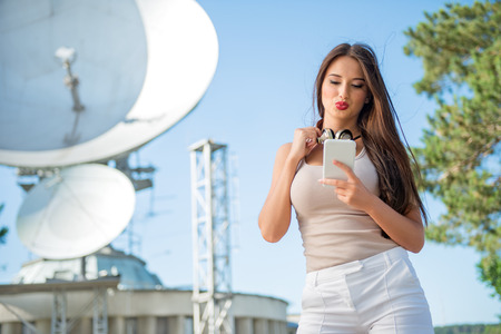 antenna: Beautiful young woman with vintage music headphones around her neck, surfing internet on a smartphone and standing against background of satellite dishes that receives wireless signals from satellites.