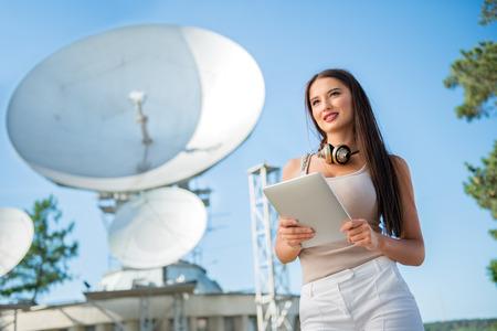 그녀의 목에 빈티지 음악 헤드폰, 태블릿 PC에서 인터넷을 서핑 및 위성으로부터 무선 신호를 수신하는 위성 접시의 배경에 서 아름 다운 젊은 여자.