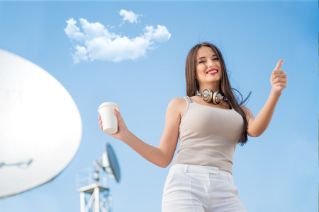 radio tower: Happy young woman wearing vintage music headphones around her neck, holding takeaway coffee and posing against background of parabolic satellite dishes that receive wireless signals from satellites.